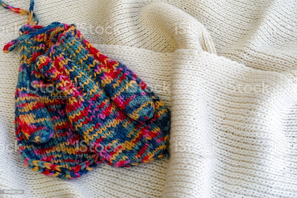 Two multicolored knitted mittens stock photo