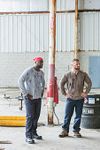 Two multi-ethnic blue collar workers in warehouse