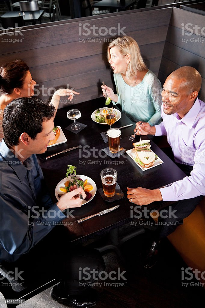 Two multiethnic couples eating in restaurant royalty-free stock photo