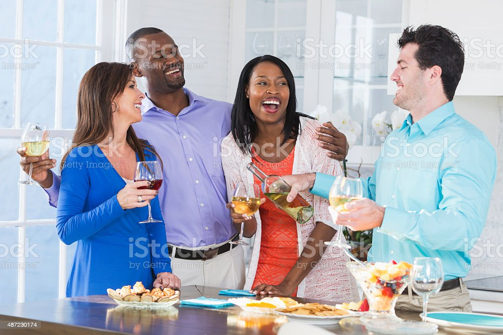 Two multi-ethnic couples enjoying wine and appetizers stock photo