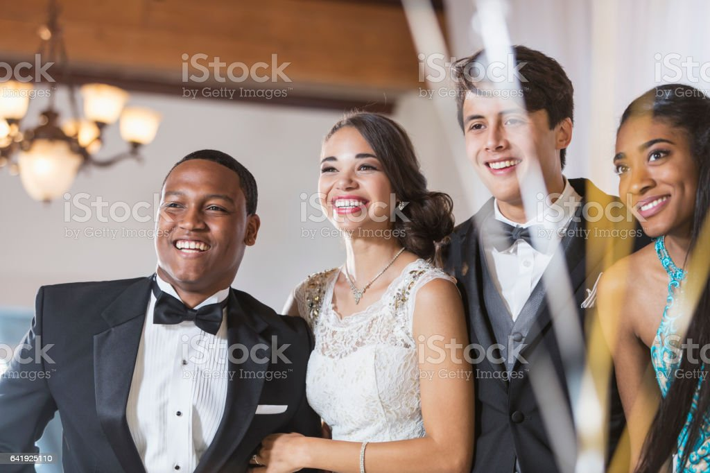 Two multi-ethnic couples in tuxedos and dresses stock photo