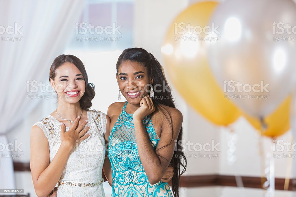Two multi-ethnic teenage girls dressed for special event stock photo