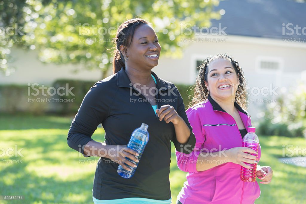 Two multi-ethnic women drinking sports drinks outdoors stock photo