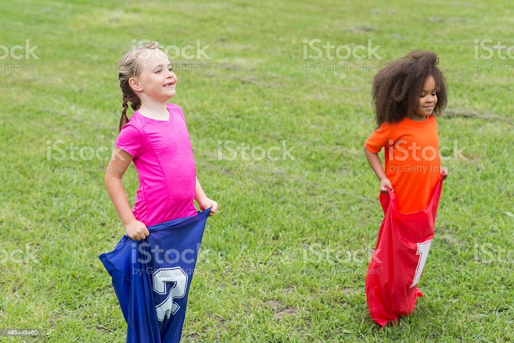 Two multiracial girls competing in a sack race stock photo