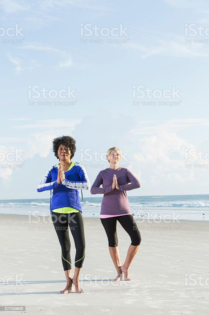 Two multi-racial mature women doing yoga on beach stock photo