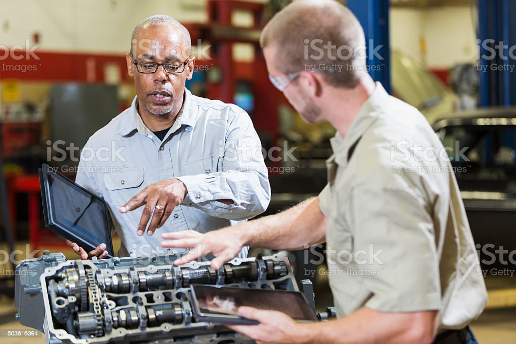 Two multi-racial mechanics with digital tablets, talking stock photo