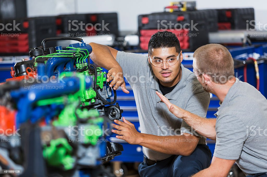 Two multi-racial men in auto mechanic school with engine stock photo