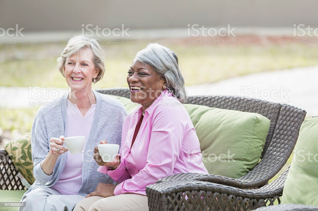 Two multiracial senior women having tea outdoors stock photo