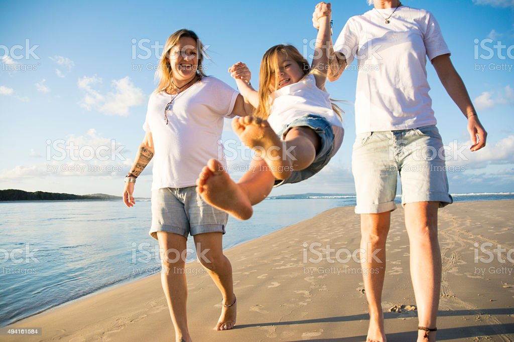 Two mum's playing with daughter at beach stock photo