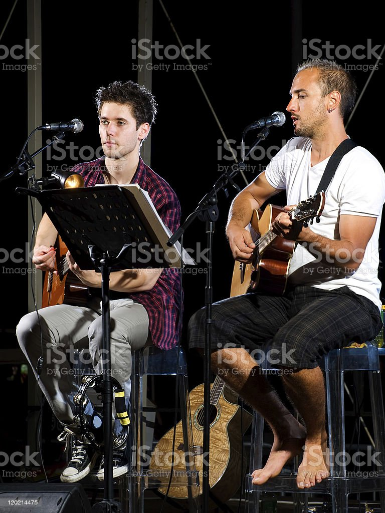 Two musicians playing guitar on a stage royalty-free stock photo
