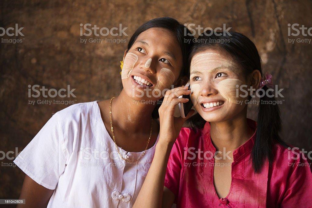 Two Myanmar girls using smart phone. royalty-free stock photo