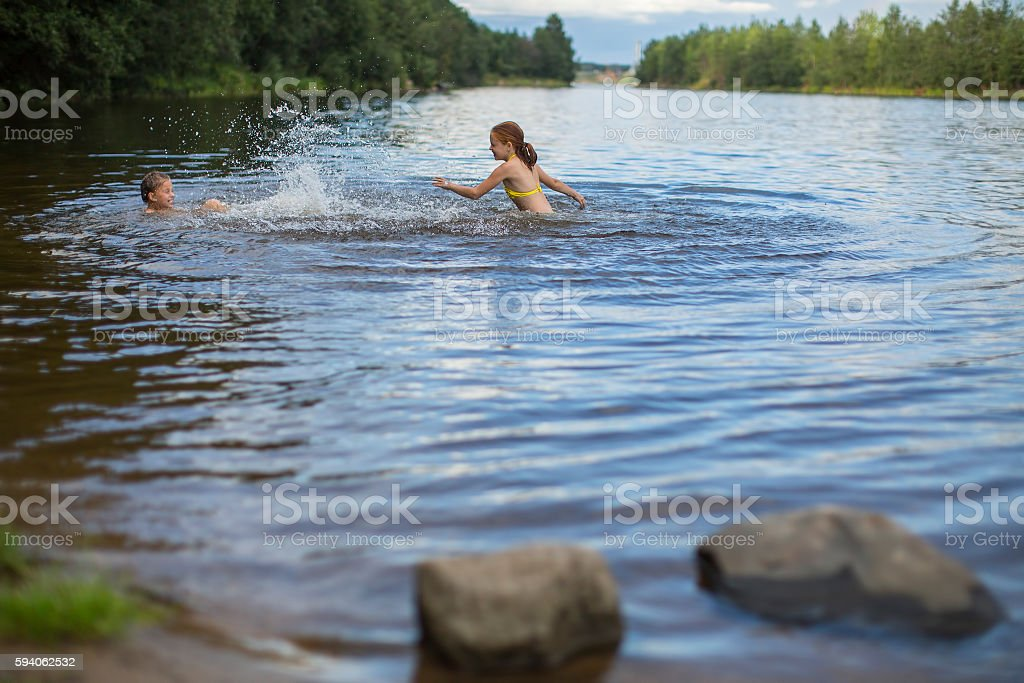 Two naughty girls bathe in the lake. stock photo