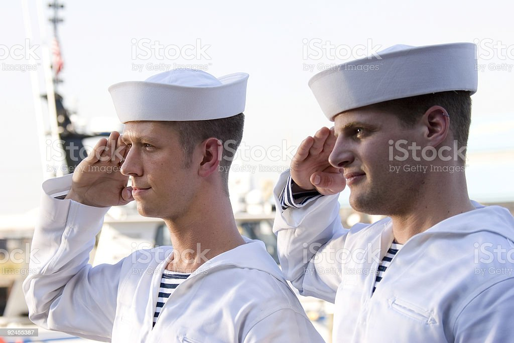 Two Navy sailors saluting on a ship stock photo