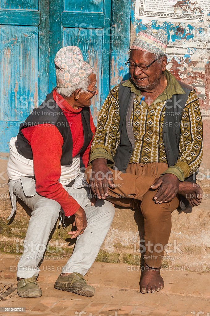 Two Nepali men, traditionally dressed, in friendly conversation, Patan, Nepal stock photo