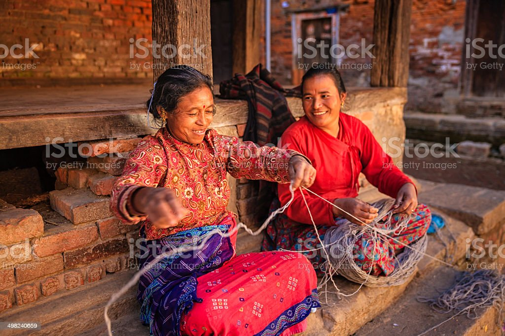 Two Nepali women  spinning a wool in Bhaktapur, Nepal stock photo