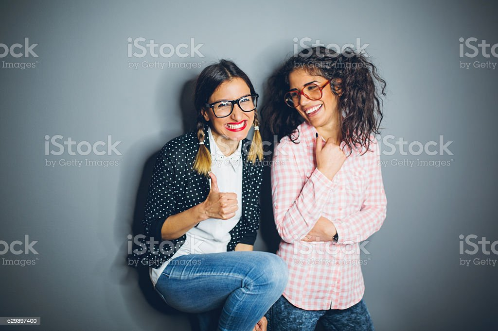 Two nerdy best friends giggling stock photo