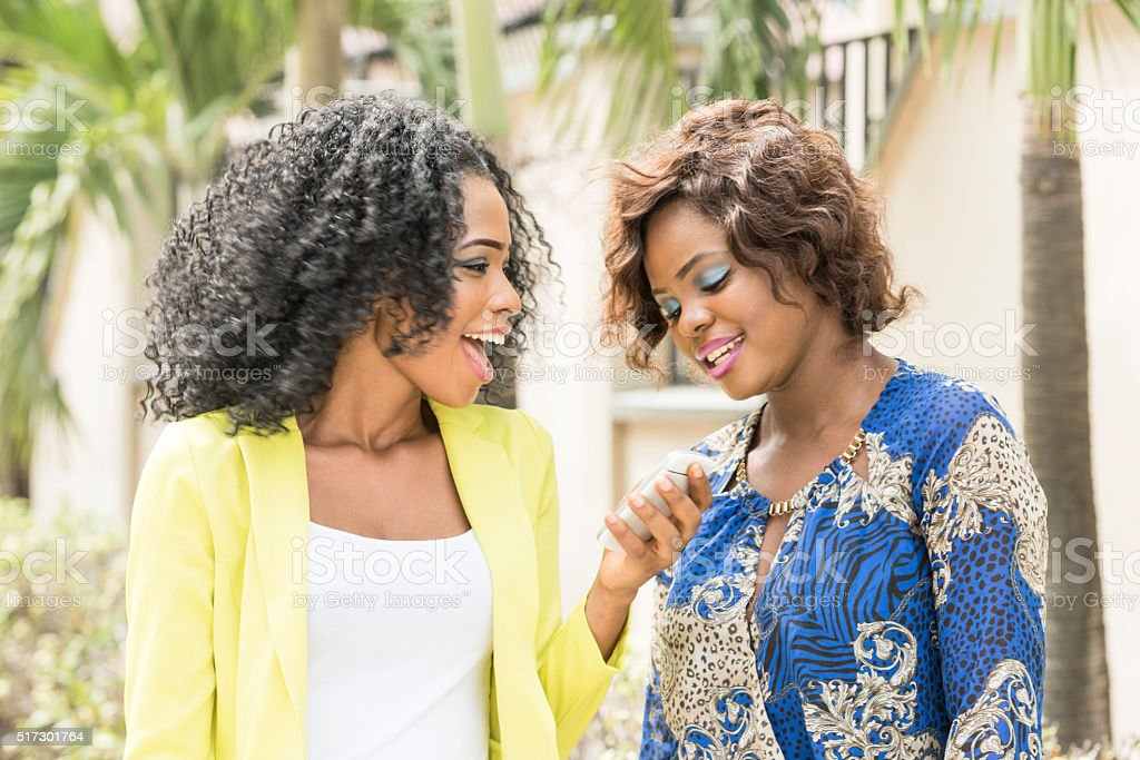 Two young African women laughing with mobile phone. Attractive Ethnic...