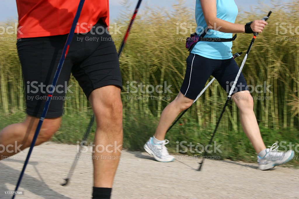 Two Nordic walkers using walking sticks in the country stock photo