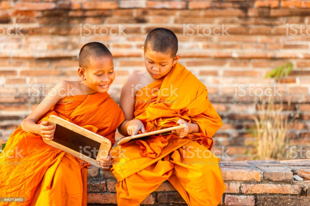 Two novice reading and studying blackboard with funny in old temple, Ayutthaya Province, Thailand stock photo