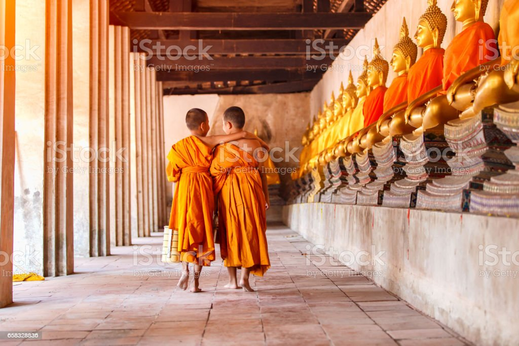 Two novices walking and talking in old temple at Ayutthaya Province, Thailand stock photo