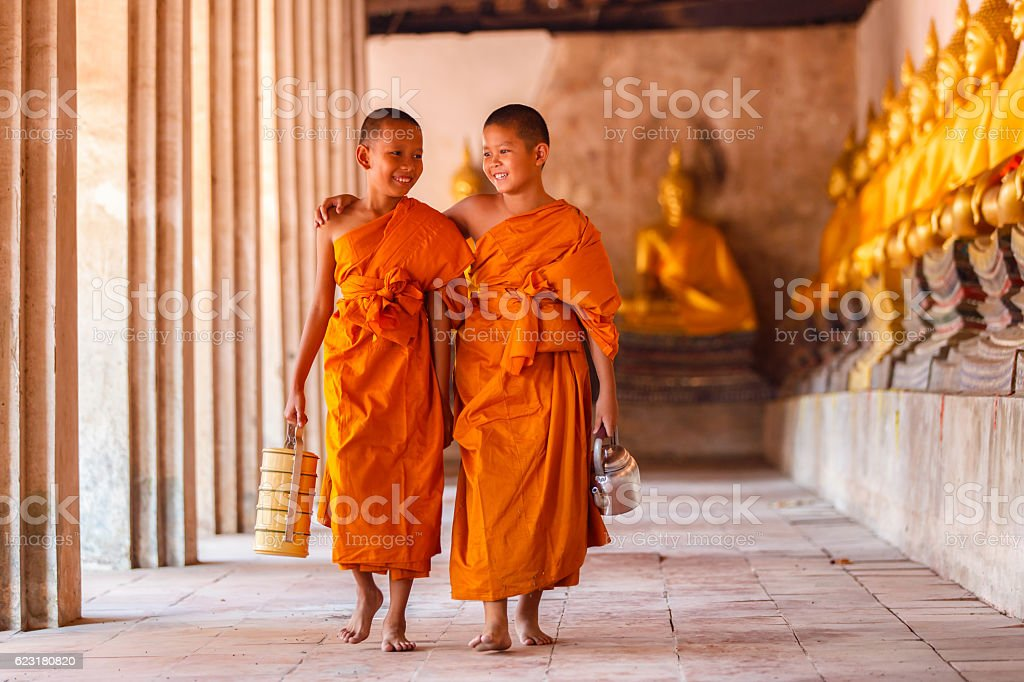 Two novices walking and talking in old temple stock photo
