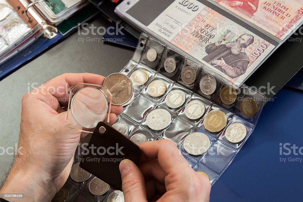Two numismatists examines  collection of coin stock photo