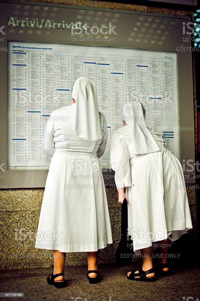 Two nuns looking at the trains schedule royalty-free stock photo