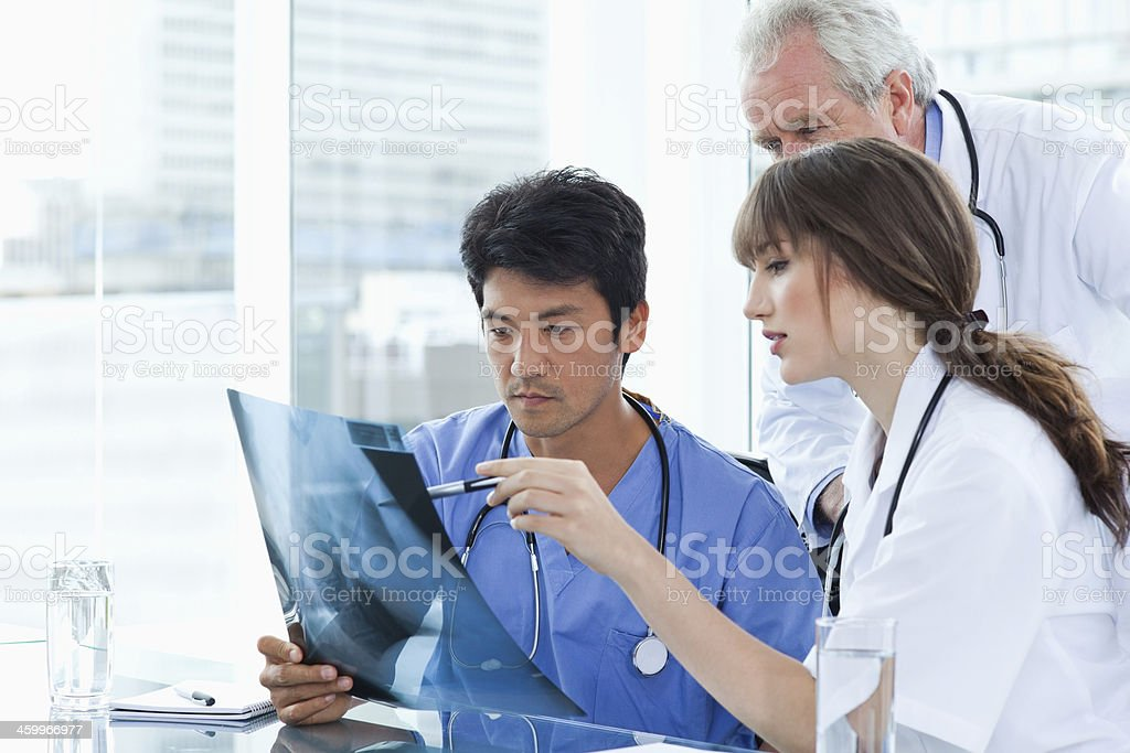 Two nurses showing an x-ray to the doctor stock photo