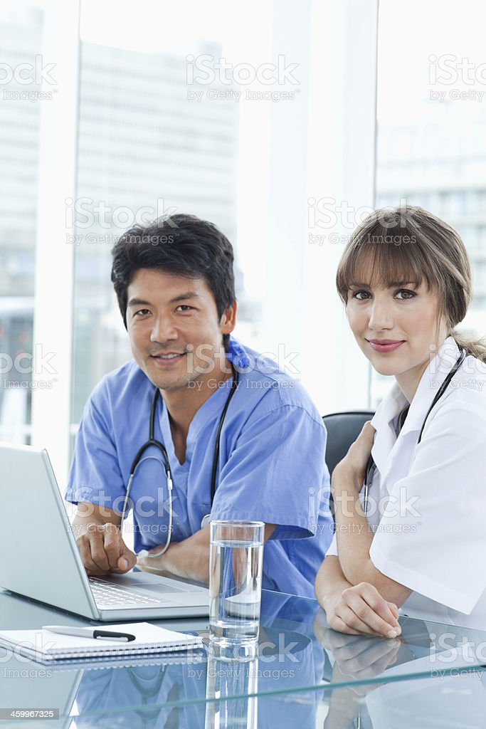 Two nurses  working seriously with a laptop while smiling stock photo