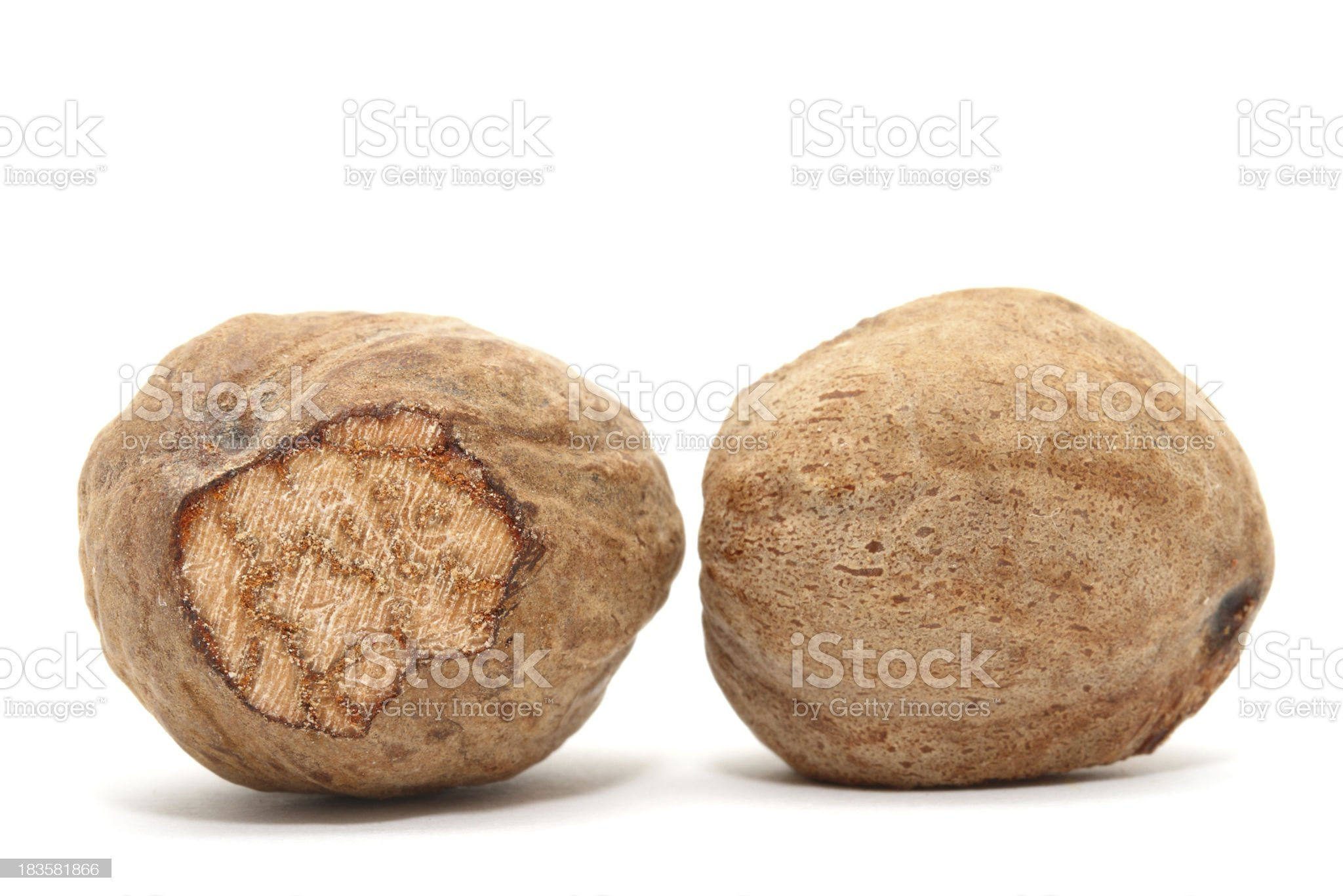 Two nutmegs on white background royalty-free stock photo