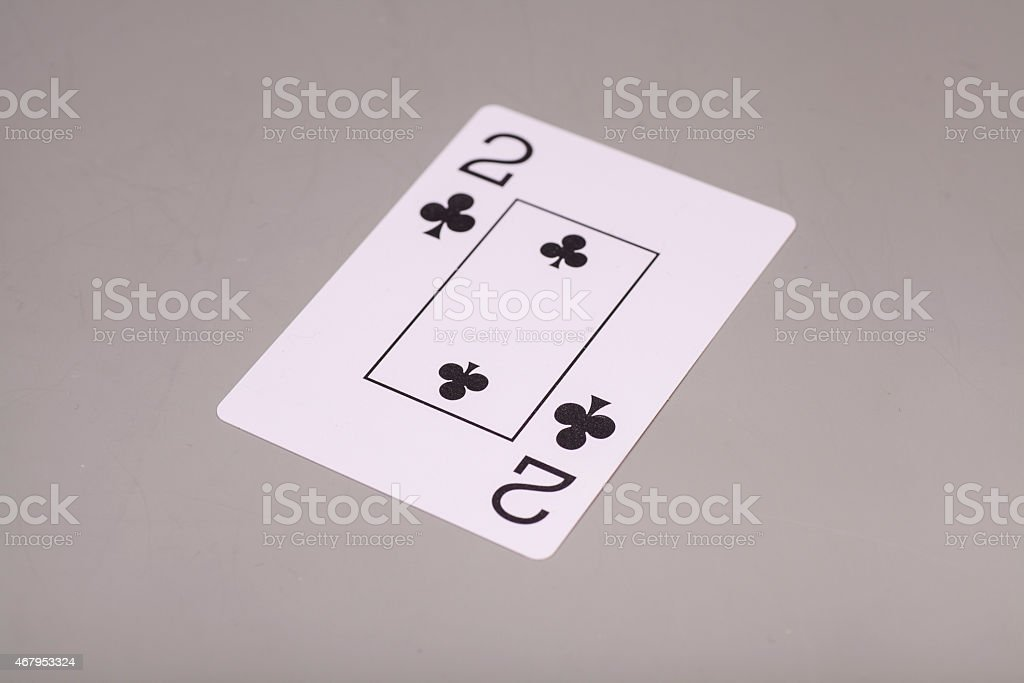 Two of clubs playing card on gray background stock photo