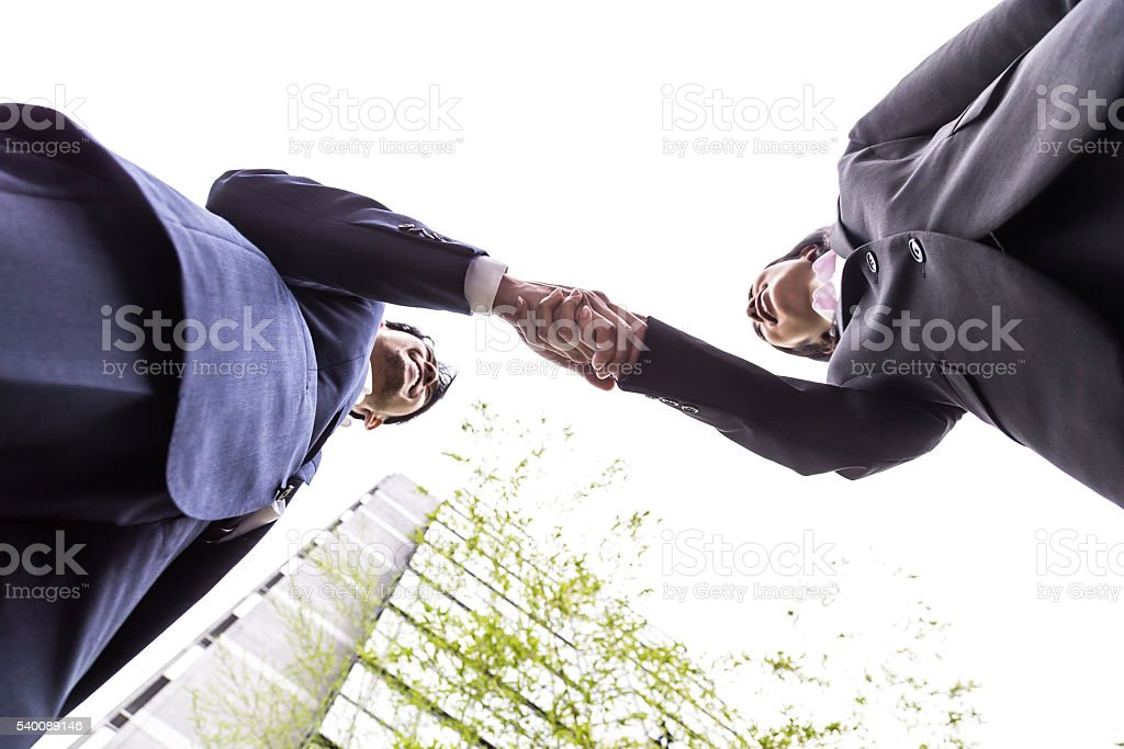 Two Office Executives Shaking Hands Over an Agreement stock photo