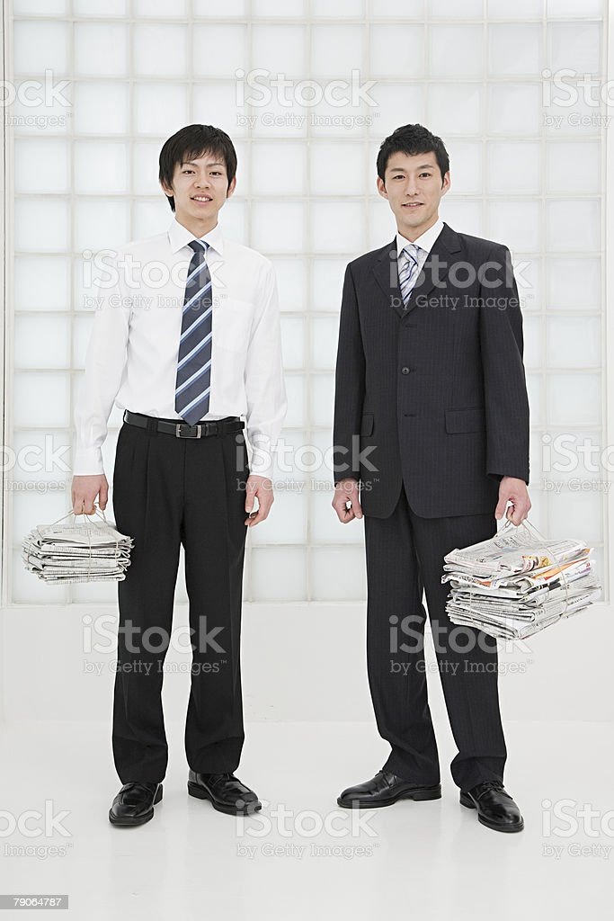 Two office workers holding newspapers royalty-free stock photo