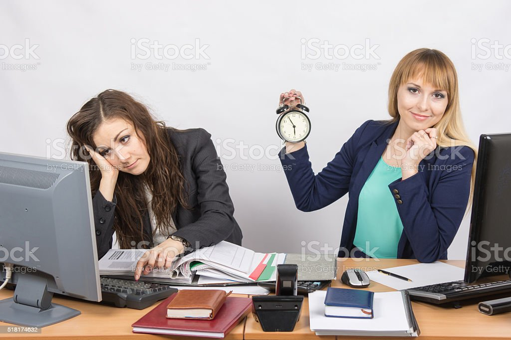 Two office workers wait for the end of working day stock photo