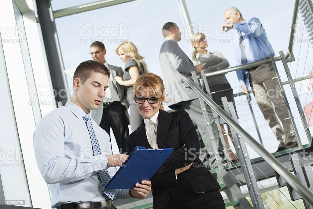 Two office workers with their colleagues in background royalty-free stock photo