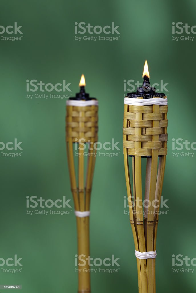 Two oil lamps burning on a green background stock photo