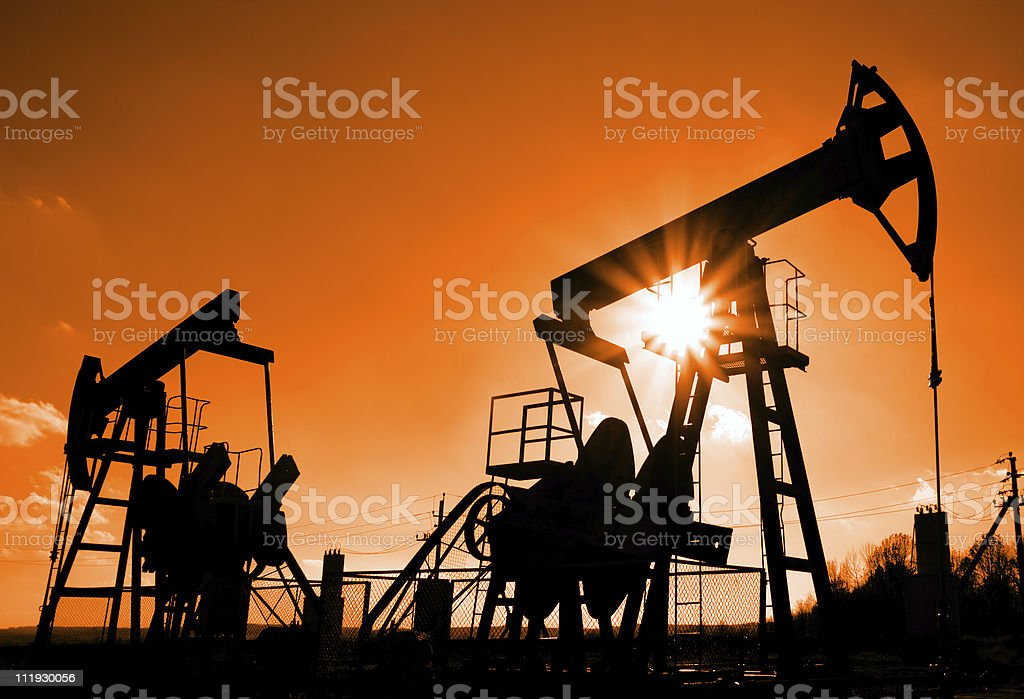 two oil pumps silhouette stock photo