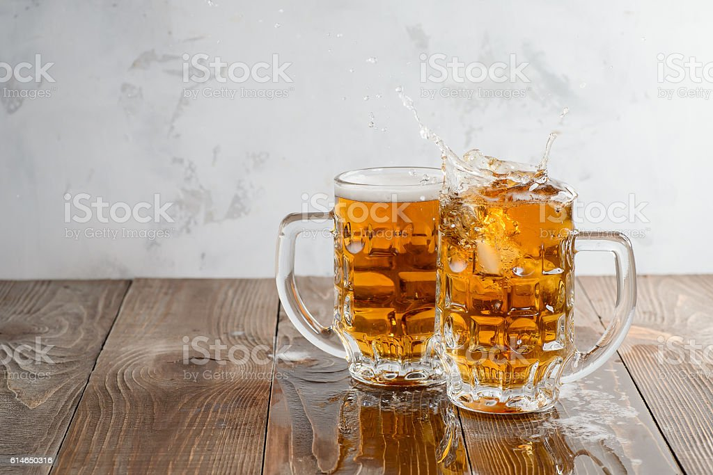 Two Oktoberfest beers splash on a wooden table stock photo
