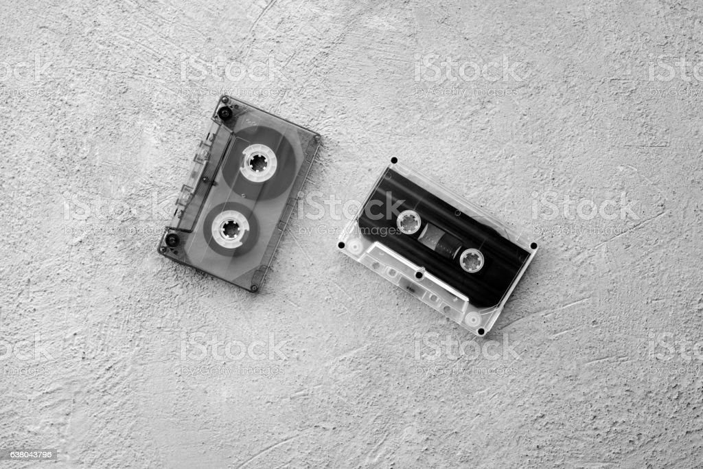 two old audio cassettes on a concrete background stock photo