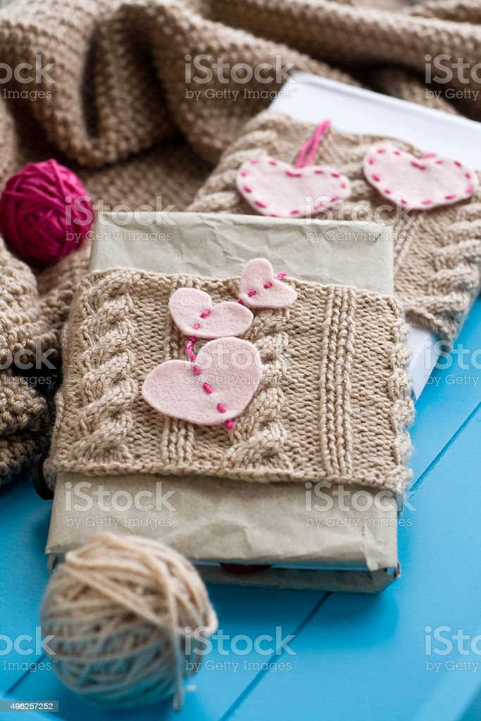 Two old pads in knitted cover with felt hearts stock photo