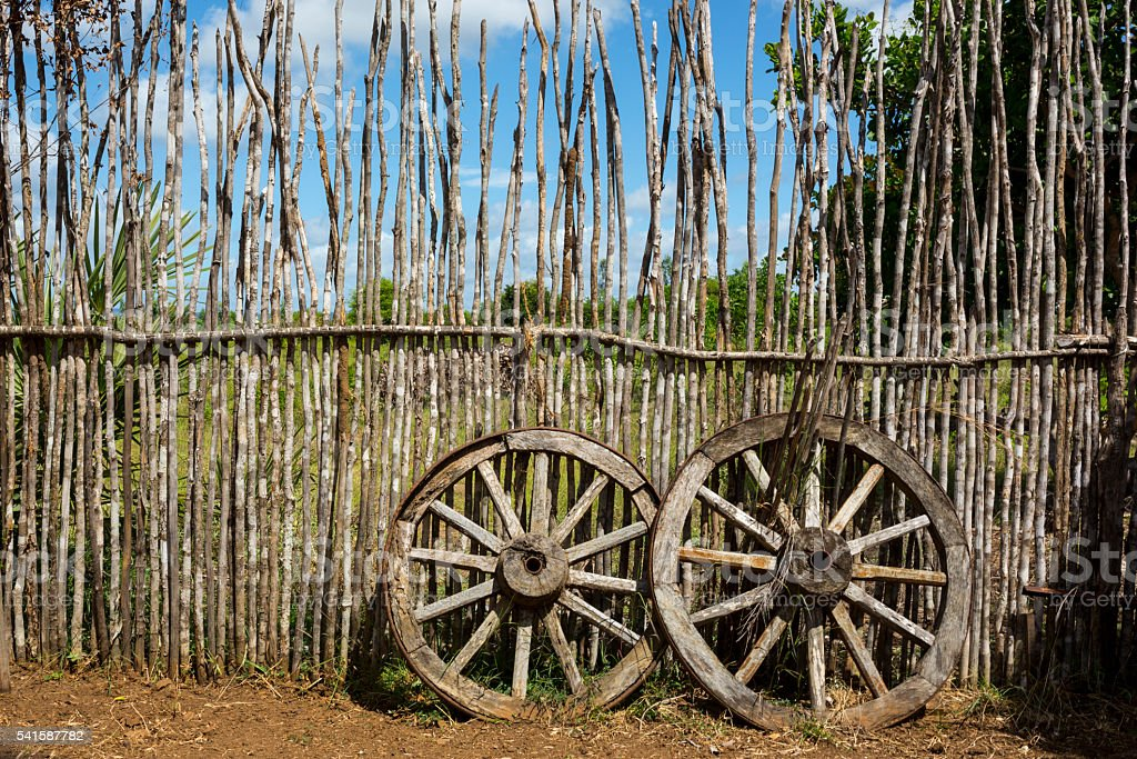 Two old waggon wheels near the wooden fence stock photo