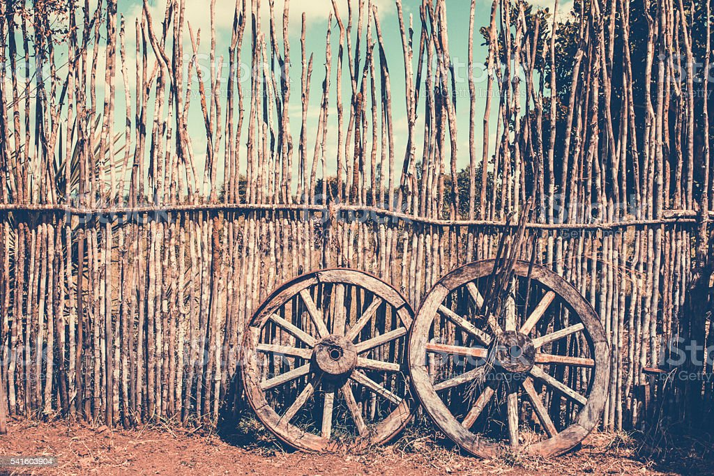 Two old waggon wheels near the wooden fence. stock photo