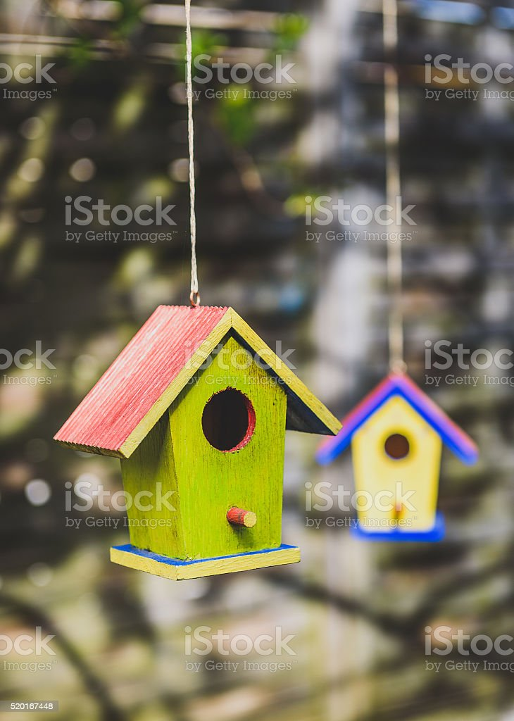 Two old weathered DIY birdhouses hanging from the tree stock photo