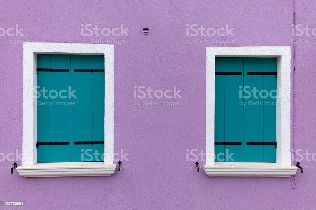 Two old windows with light blue shutters on violet wall stock photo