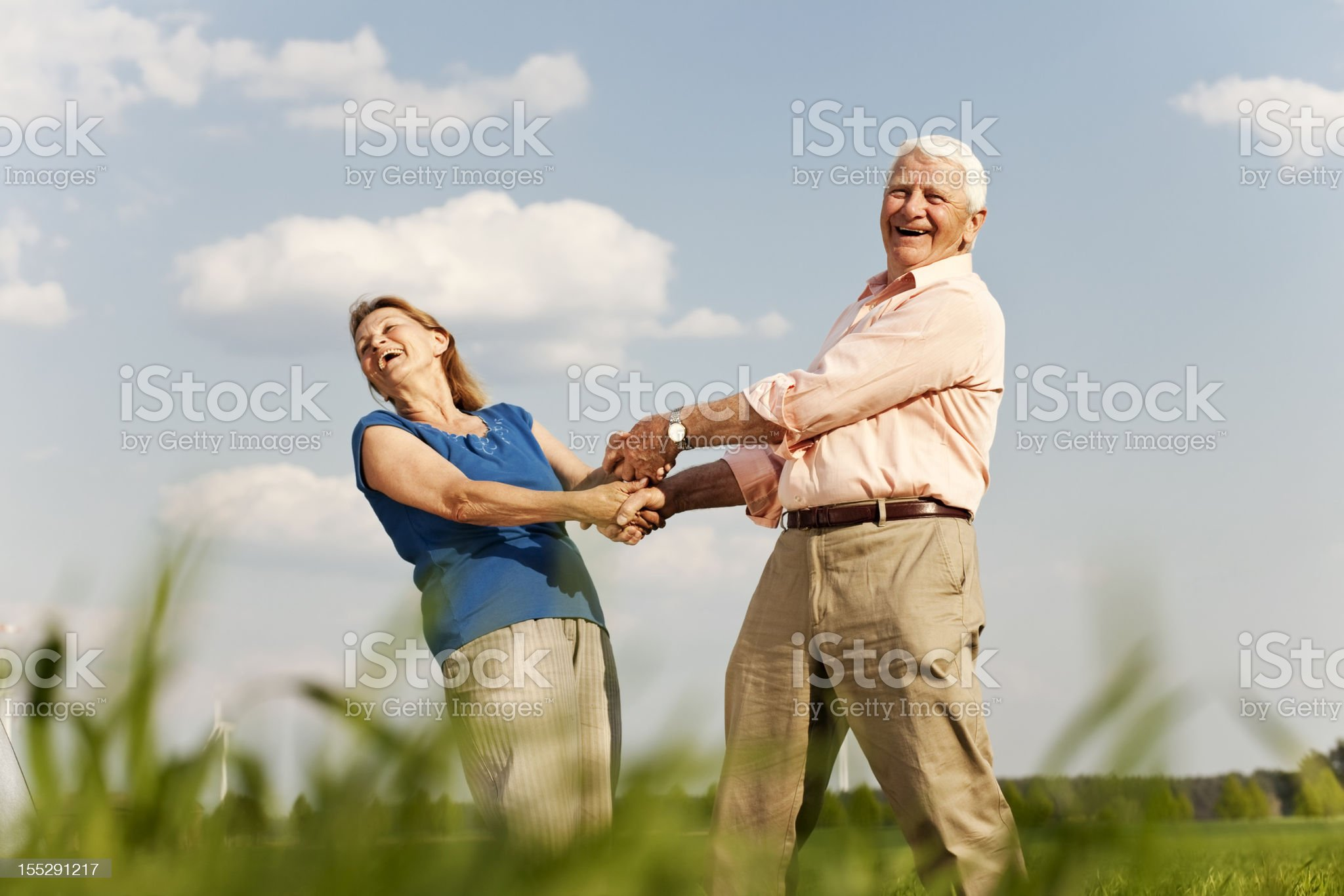 Two older people holding hands and spinning outside  royalty-free stock photo