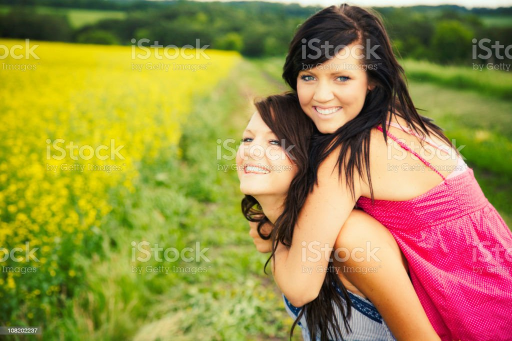 Two Older Sisters Playing and Standing in Canola Field royalty-free stock photo