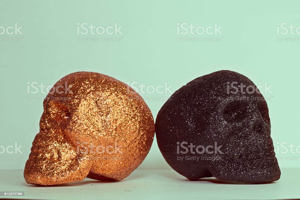 Two Orange and Black Colorful Skull Heads on Green Background stock photo