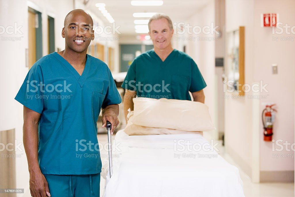 Two Orderlies Pushing An Empty Bed Down A Hospital Corridor stock photo
