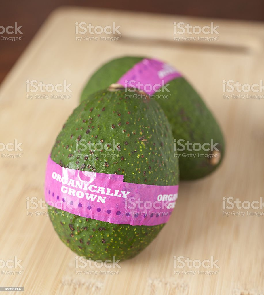 Two Organic Avocados on a Cutting Board stock photo