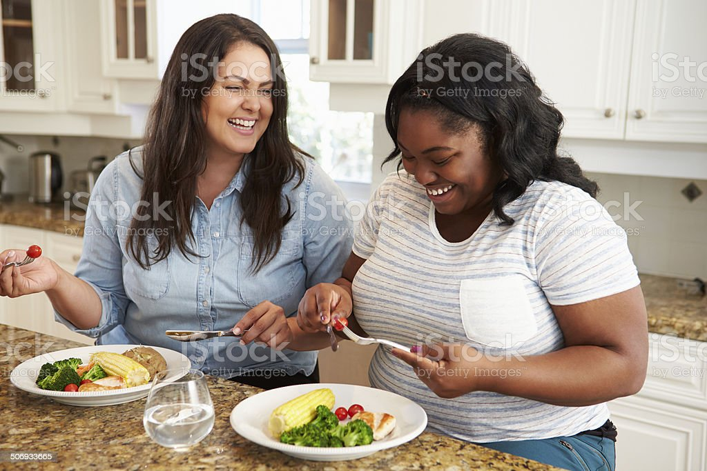Two Overweight Women On Diet Eating Healthy Meal In Kitchen stock photo